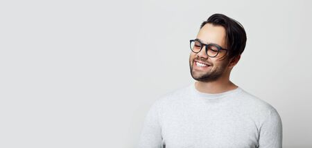 Portrait of young smiling man with white teeth on white background, wearing eyeglasses.