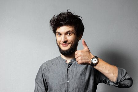Portrait of young bearded satisfied guy with disheveled hair, shows thumbs up on background of grey.