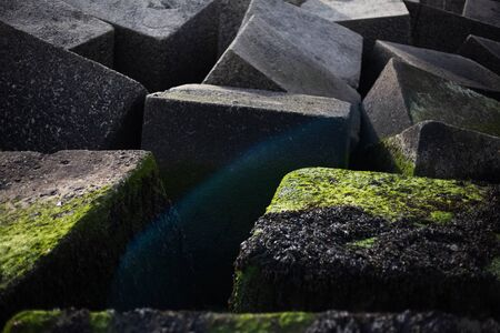 Artistic image of big stoned cubes on the seaside. Stock Photo