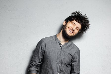 Portrait of young happy bearded guy with disheveled hair on grey background.