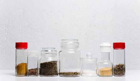 Different seasoning in glass cups, on white background.