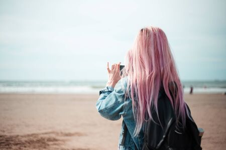 Back view of young girl with pink hair and black backpack admiring the sea with smartphone in hand.