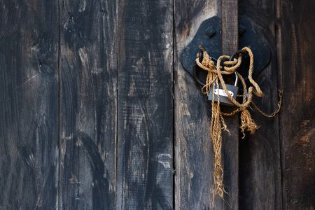Close lock on the ancient door with rope.