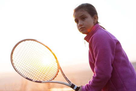 Portrait of teenage girl is training tennis skill outside court, in field at sunset. Wearing pink sweater and holding tennis racket.