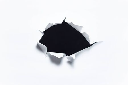 Abstract background of dark torn hole in white paper.