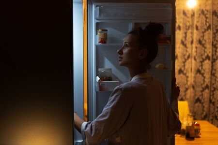Young girl looking in fridge at night.