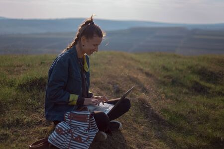 Portrait of young hipster girl in denim jacket, using laptop with earphones in backpack on background of sunset in field.