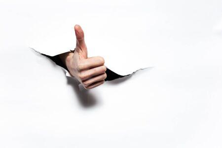 Thumb up through dark hole of white paper.