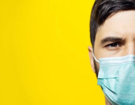 Close-up portrait of male face, wearing medical flu mask on background of yellow color with copy space.