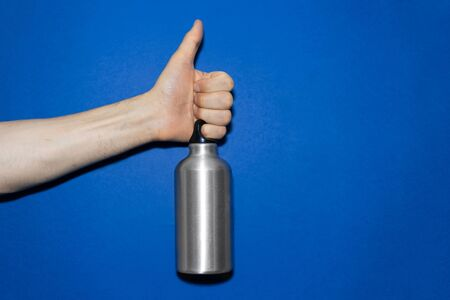 Close-up of male hand holding aluminum water bottle, showing thumbs up, on background of phantom blue color.