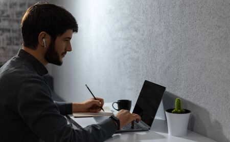 Young businessman typing on keyboard of laptop, making notes, using wireless earphones. Coffee mug and cactus on work desk. Copy space background of grey color. Stockfoto