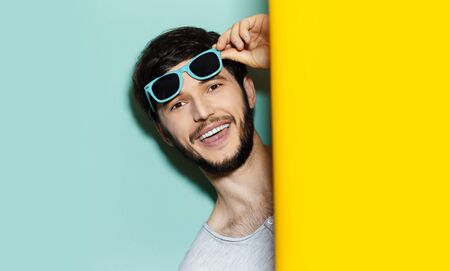 Studio portrait of young happy guy with blue shades on his head, comes out between two background of yellow and aqua menthe colors.
