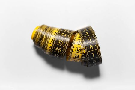 Close-up of black and yellow measuring tape isolated on white background with shadows. Banque d'images