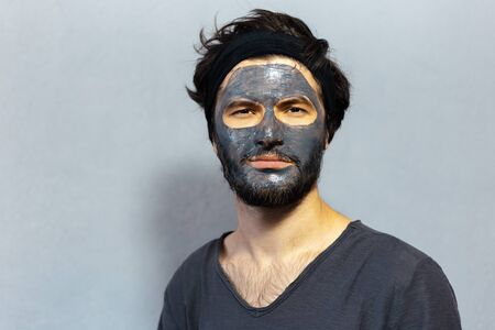 Portrait of young disheveled guy with beauty facial mask on background of grey background. Imagens