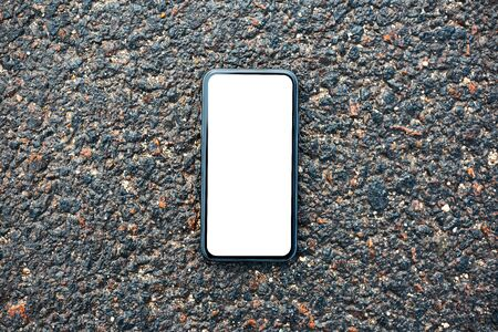 Close-up of modern smartphone with mockup on background of wet asphalt.