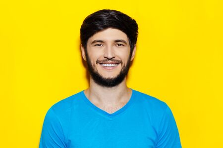 Studio portrait of young smiling guy wearing blue shirt on background of yellow color. 版權商用圖片