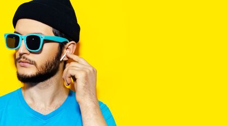 Studio portrait of young hipster man in blue shirt, wearing cyan sunglasses and black beanie hat, using wireless earphones on background of yellow color with copy space. 版權商用圖片