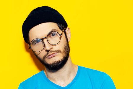 Studio portrait of young hipster guy wearing black beanie hat and round eyeglasses on background of yellow color.