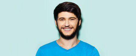 Studio portrait of young smiling guy in cyan shirt on background of aqua menthe color. Panoramic banner view.