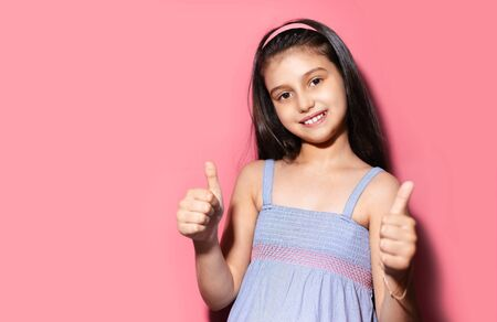 Studio portrait of smiling child girl showing thumbs up on background of pastel pink of color.