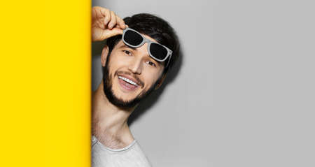 Studio portrait of young happy man between two backgrounds of grey and yellow colors with copy space. Wearing sunglasses.