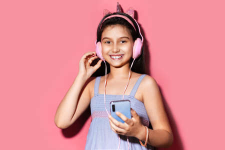 Studio portrait of happy little child girl, holding smartphone in hands, using headphones. Background of pastel pink color. Wearing blue dress.