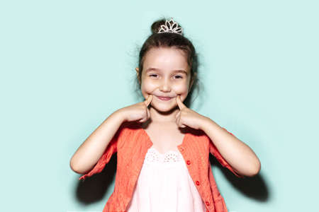 Studio portrait of happy little child girl pointing with fingers on cheeks. Background of aqua menthe color. Wearing coral shirt and princess crown.