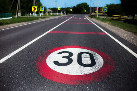 30km/h speed limit sign painted on asphalting road.