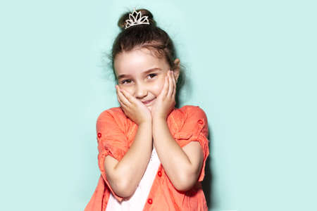 Studio portrait of shy little child girl, holding palms on cheeks. Background of aqua menthe color. Wearing coral shirt and princess crown.