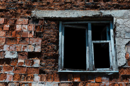 Abandoned redbrick building. Close-up of wooden window.