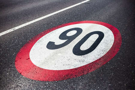 90km/h speed limit sign painted on asphalting road.