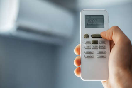 Close-up of male hand holding remote control of air conditioner.
