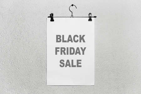 Black friday sale text on white paper, attached to cloth hanger on the grey textured background. Stock fotó