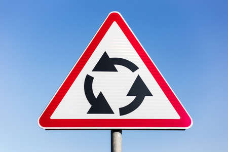 Close-up of roundabout road sign on background of blue sky. Stock Photo