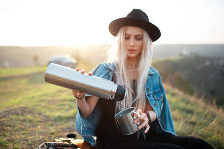 Portrait of young teenage blonde girl, pouring tea into the steel cup from bottle. Outdoor background of sunset. Wearing black hat and denim jacket. Stok Fotoğraf