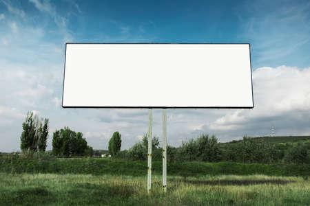 Empty billboard for advertising poster in green field omn background of blue sky.