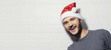 Portrait of young happy man with Santa Hat on background of white brick wall with copy space. Christmas concept.