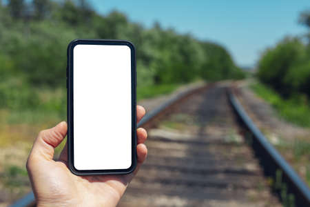 Close-up of male hand holding smartphone with mockup background of blurred railway.