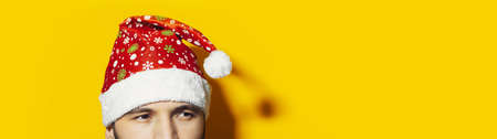 Panoramic portrait of young man wearing santa hat on background of yellow color with copy space. Christmas concept. Stok Fotoğraf