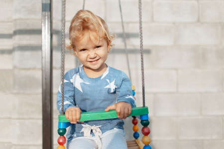 Portrait of smiling child girl sitting on carousel on the outdoor playground for kids. Stok Fotoğraf