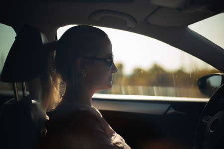 Side portrait of woman driving. Wearing sunglasses.
