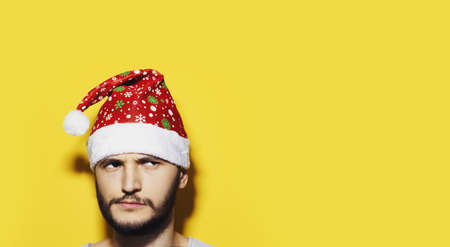 Studio portrait of young thoughtful man looking up, wearing Santa Hat. Background of yellow color with copy space. Christmas  concept.