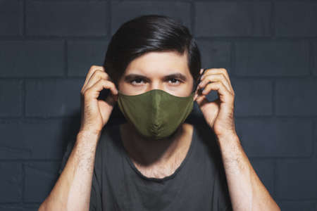 Portrait of young man, wearing respiratory mask on face against coronavirus and covid-19. Background of black brick wall. Stok Fotoğraf
