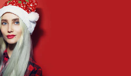 Studio portrait of young blonde girl wearing Santa Hat on background of red color with copy space. Christmas concept.