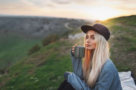 Portrait of young blonde girl with black cap, holding steel mug with hot tea on background of sunset. Stok Fotoğraf