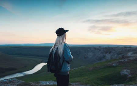 Back view of blonde girl with black backpack and cap. Young traveler looking at sunset from the hills.