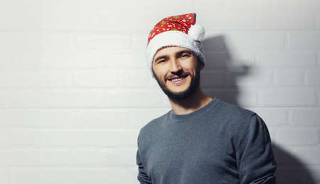 Studio portrait of young smiling guy on background of white brick wall. Christmas concept. Wearing red Santa Hat and grey sweater.