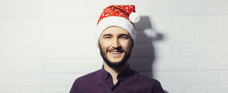 Panoramic portrait of young smiling guy, wearing Santa Hat on background of white brick wall. Christmas holidays concept.
