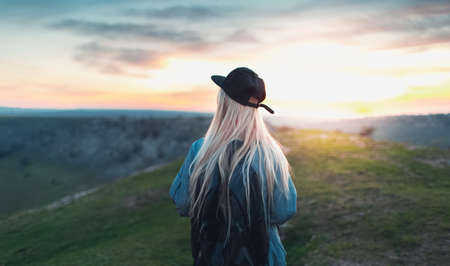 Back view of young blonde girl with black cap and backpack, walking on peak of the hills. Background of sunset.