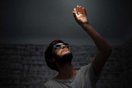 Dark portrait of young guy, looking up and touching the light. Wearing sunglasses. Using wireless earphones. Stok Fotoğraf